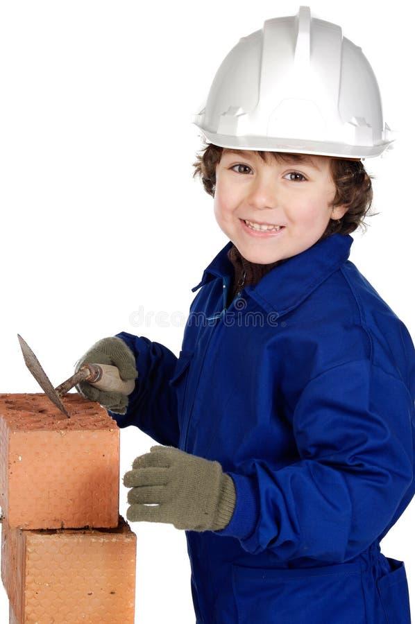 tegelstenbyggmästarebarn som gör väggen royaltyfri foto