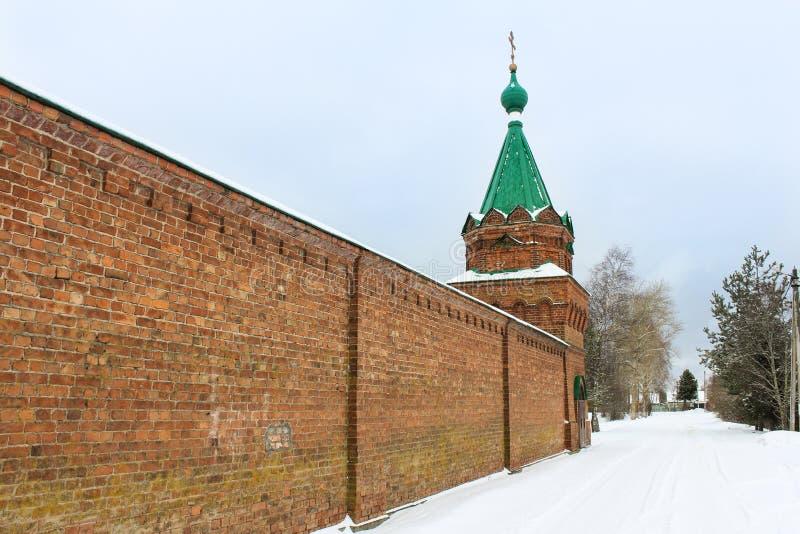 Tegelstenklostervägg med ett torn royaltyfri foto