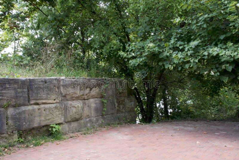 Tegelstenplaza med stenväggen royaltyfri bild