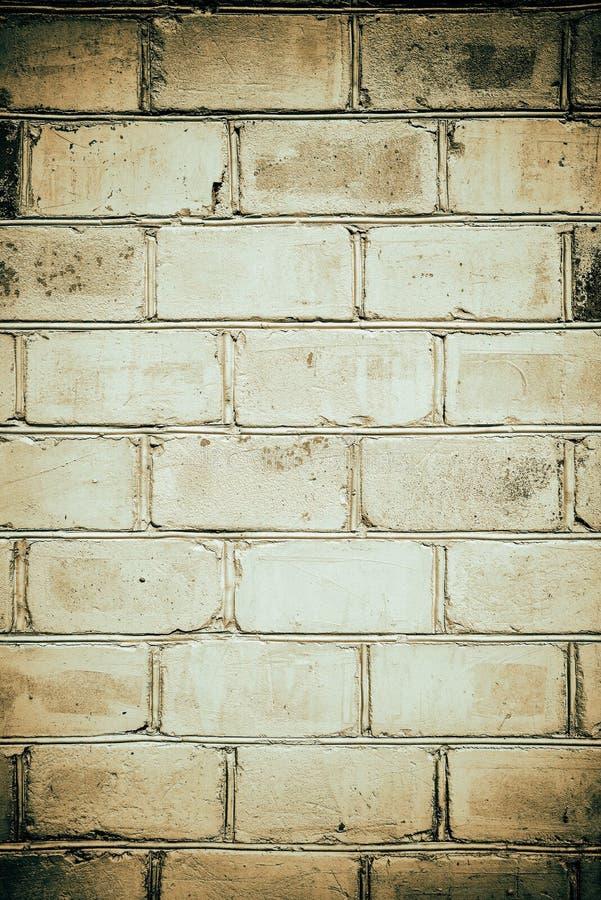 Tegelstenvägg i grungestil, senapsgult färgeffekt, tapet eller bakgrund med stället för text arkivfoto