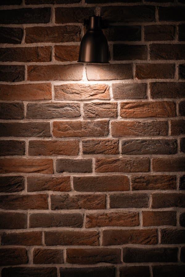 Tegelstenvägg med en lampa arkivfoton