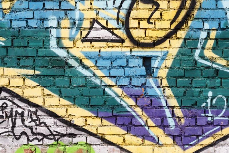 Tegelstenvägg med grafitti arkivfoto