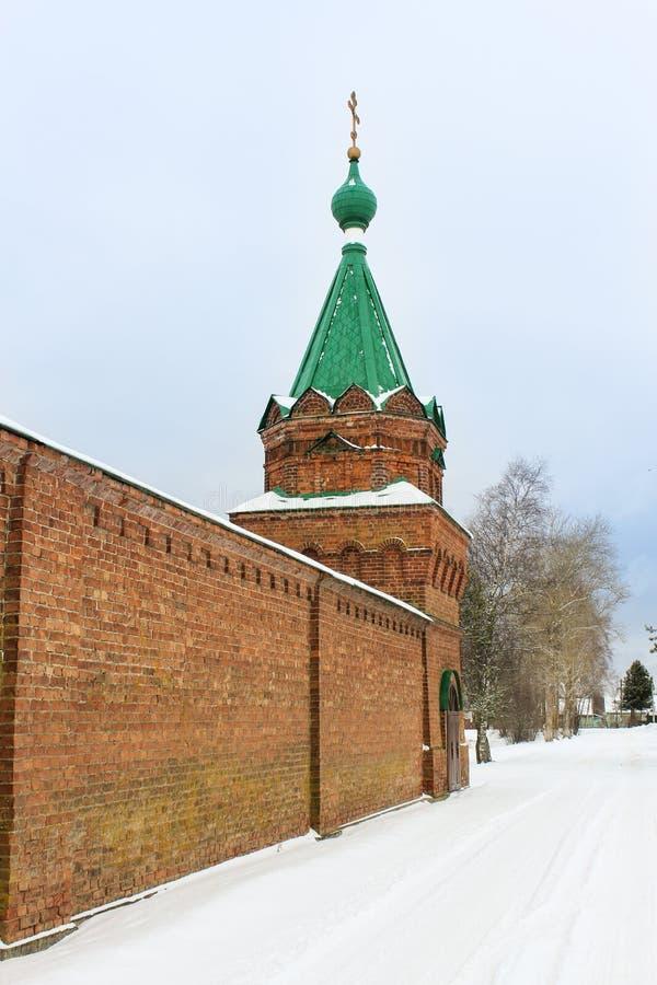 Tegelstenvägg med tornet av kloster arkivbild