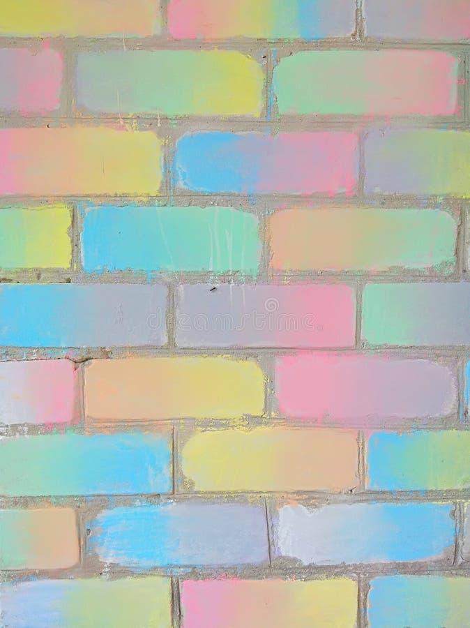 Tegelstenvägg som dekoreras med kulör krita, lutning, bakgrund royaltyfria bilder