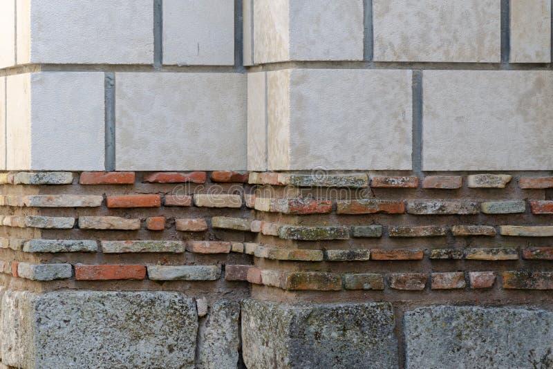 Tegelstenvägg som göras av kvarter med olikt färg och format arkivfoto