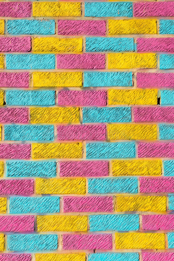 Tegelstenvägg som målas i ljusa guling-, blått- och rosa färgfärger arkivbilder