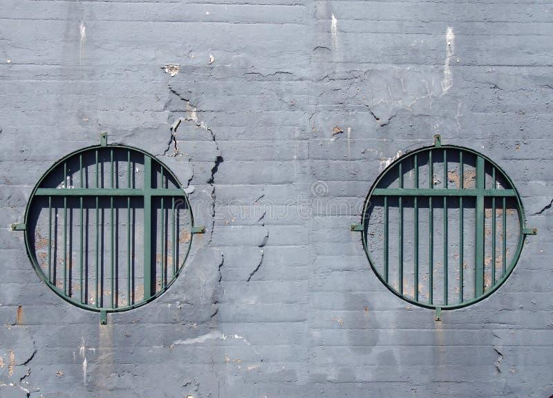 Tegelstenväggen med urblekta grå färger knäckte skala målarfärg med två runda blockerade fönster med gröna rosta metallstänger royaltyfria foton