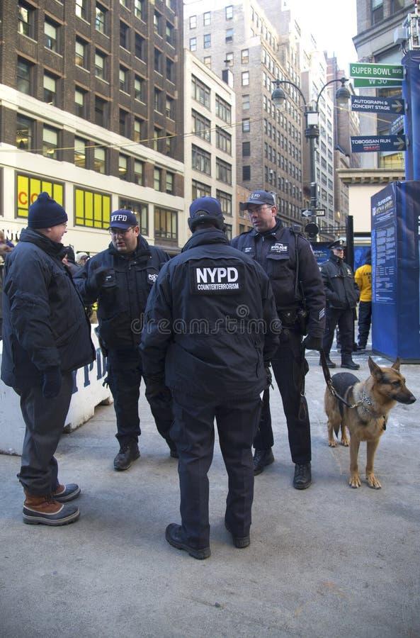 Tegen het terrorismeambtenaren van NYPD en NYPD-doorgangsdienst k-9 politieman met hond k-9 die veiligheid op Broadway verstrekken stock foto's