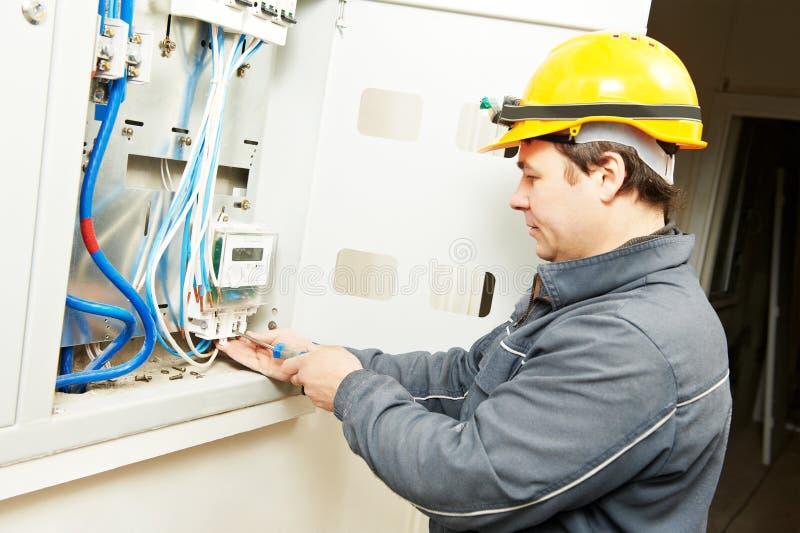 Tegenmeter van de elektricien de verbindende elektriciteit in zekeringkast royalty-vrije stock afbeeldingen