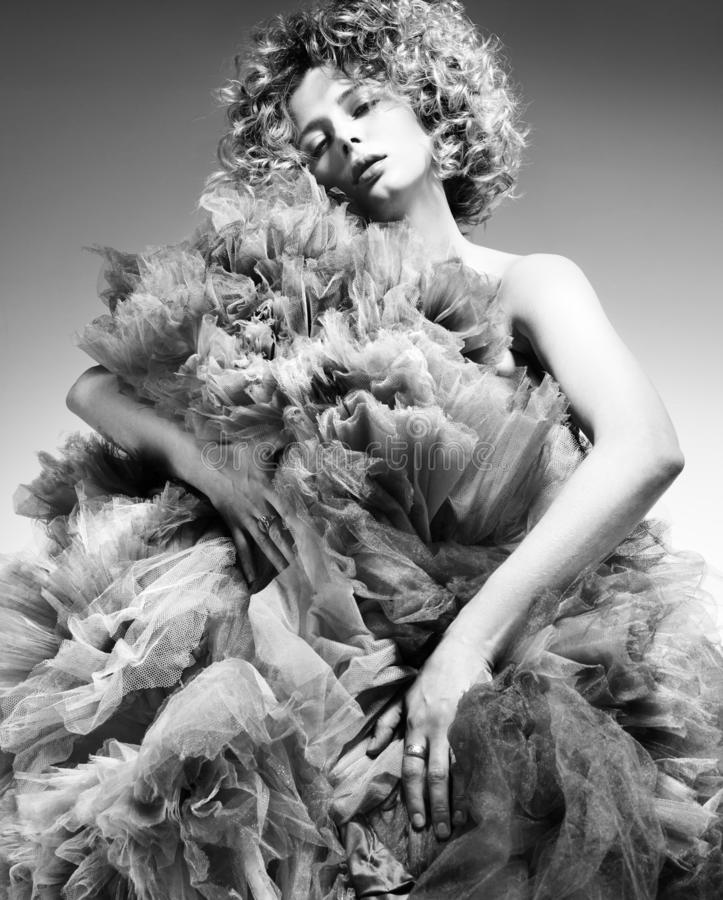 Tegenover elkaar stellend zwart-wit manierportret van een jonge vrouw in een weelderige kleding royalty-vrije stock foto's