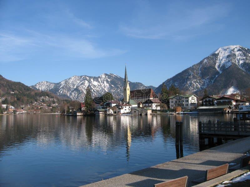 Tegernsee sikt av kyrkan på sjön med de bayerska fjällängarna arkivbild