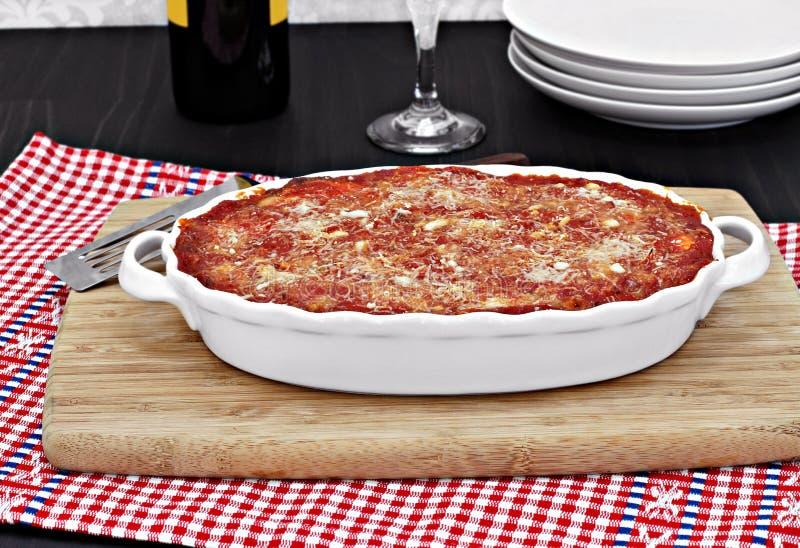 Teglia da forno bianca ovale piena di melanzana al forno o di lasagne al forno immagine stock libera da diritti