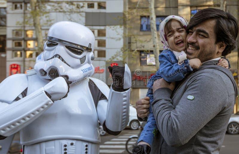 Teheran, Iran - 2019-04-03 - Barnet är skrämt när fader Hands till Star Wars Storm Trooper Character på gatan royaltyfri bild