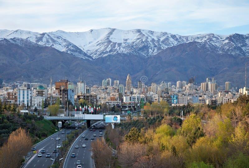 Teheran-Skyline und Landstraße vor Snowy-Bergen stockbild