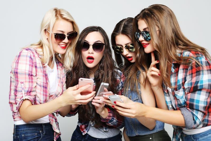 Tehnology, emoção e conceito dos povos: quatro amigos felizes das mulheres que compartilham de meios sociais em um telefone esper fotografia de stock royalty free