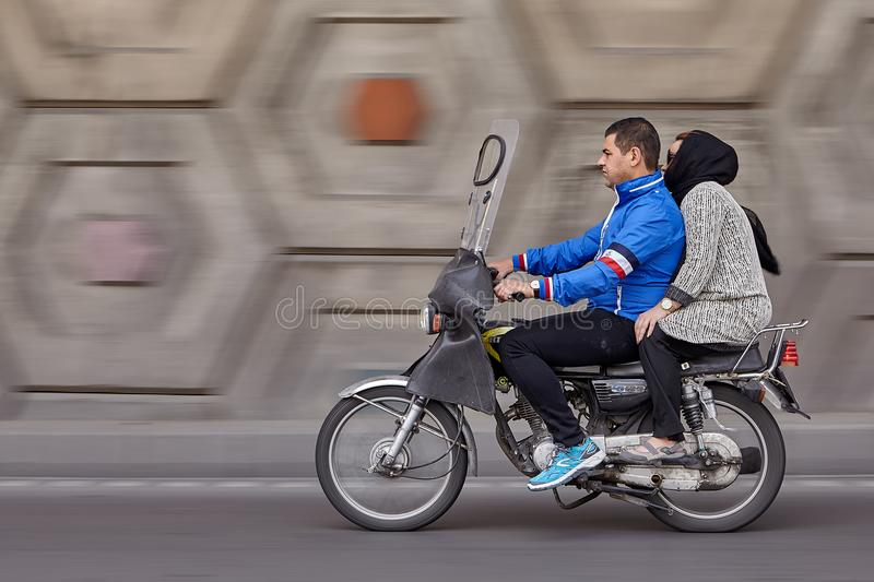 Married couple riding motorcycle on speedway, panning for motion. Tehran, Iran - April 28, 2017: Panning motorbike with man and woman at speed, to create motion royalty free stock photos