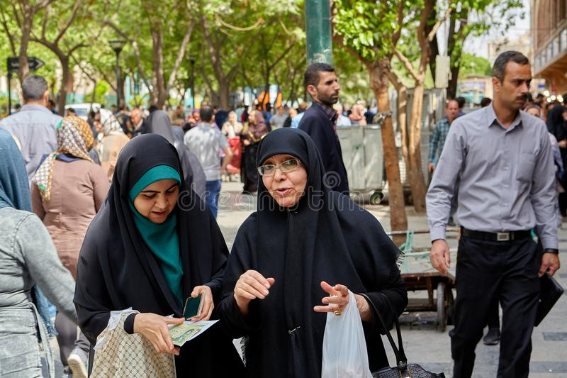 Two Muslim women talk on busy street of Tehran, Iran. royalty free stock images