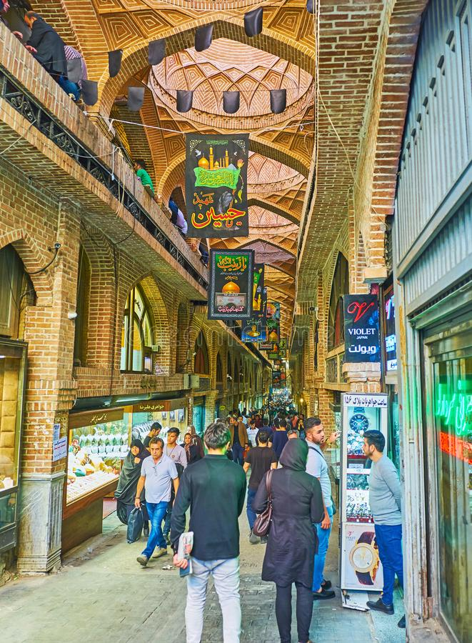 In Bazaar-e Bozorg, Tehran. TEHRAN, IRAN - OCTOBER 11, 2017: The crowded row of Bazaar-e Bozorg Grand Market with multiple brick domes and bright showcases of royalty free stock images