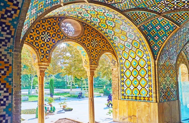 Idyllic views of Golestan, Tehran. TEHRAN, IRAN - OCTOBER 11, 2017: The shady green garden of Golestan palace is seen through the arches of Karim Khani Nook, the royalty free stock image