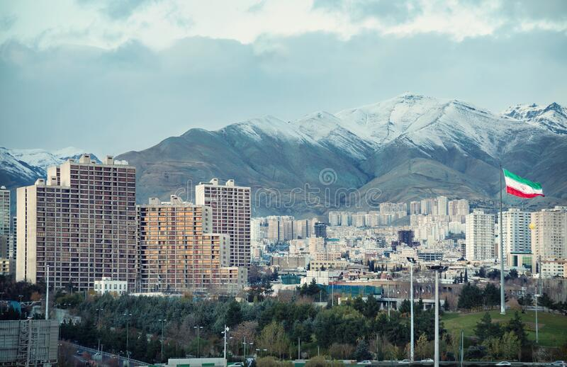 Tehran Skyline with Iran Flag and Alborz Mountains stock photography