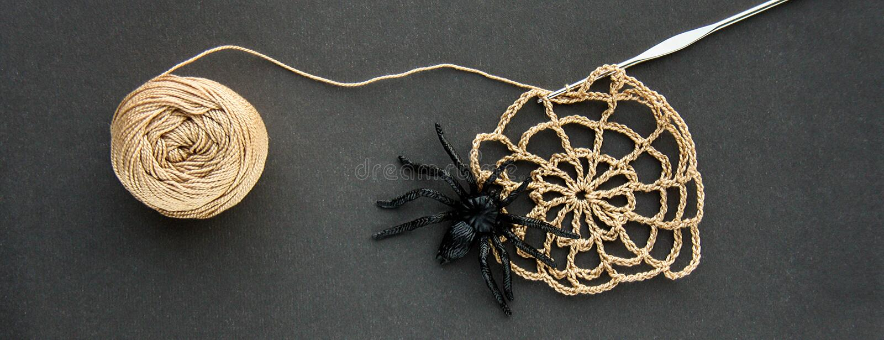 A teia de aranha feita crochê com a aranha de borracha preta, faz crochê e a bola do fio de algodão das linhas no fundo de papel  fotos de stock royalty free