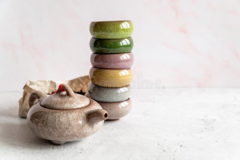 Teiera asiatica con un mucchio dei tazza da the variopinti ed il pacchetto di tè su fondo di marmo bianco fotografie stock