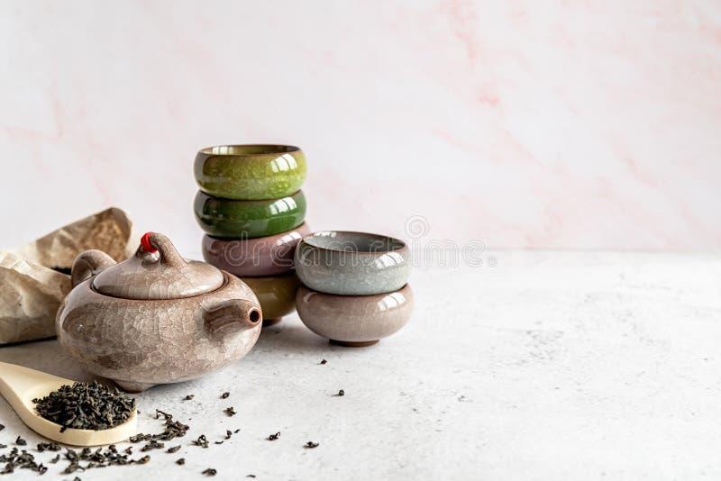 Teiera asiatica con un mucchio dei tazza da the variopinti ed il pacchetto di t? su fondo di marmo bianco immagini stock libere da diritti