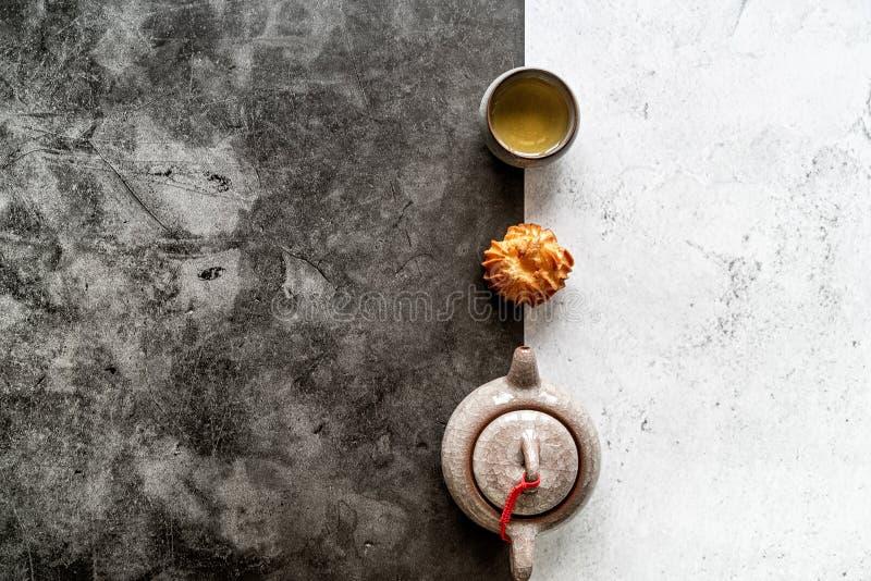 Teiera asiatica del tè, tazza e un dolce sulla disposizione piana doppia bianca e nera di vista superiore del fondo fotografia stock