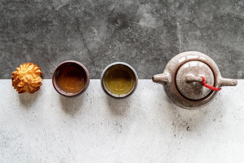 Teiera asiatica del tè, tazze e un dolce sulla disposizione piana doppia bianca e nera di vista superiore del fondo immagini stock libere da diritti