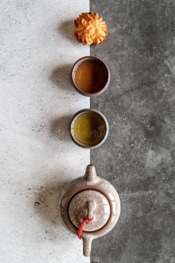 Teiera asiatica del t?, tazza e un dolce sulla disposizione piana doppia bianca e nera di vista superiore del fondo immagine stock libera da diritti