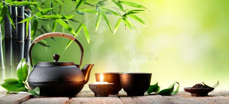 Teiera asiatica e tazze del ferro nero fotografia stock