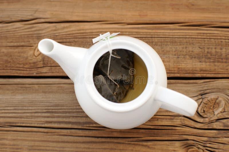 Teiera bianca con due bustine di tè della piramide su fondo di legno fotografia stock libera da diritti