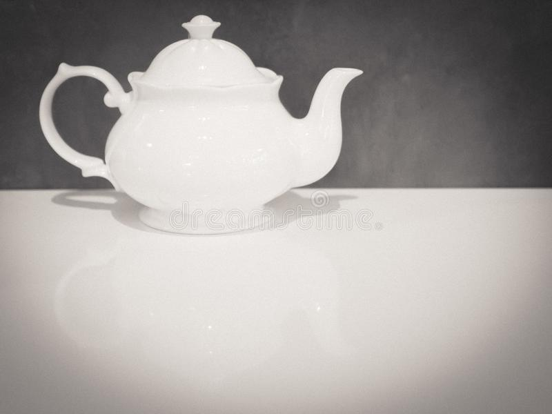 Teiera britannica bianca della porcellana sul tono adorabile del fondo grigio bianco della tavola fotografia stock