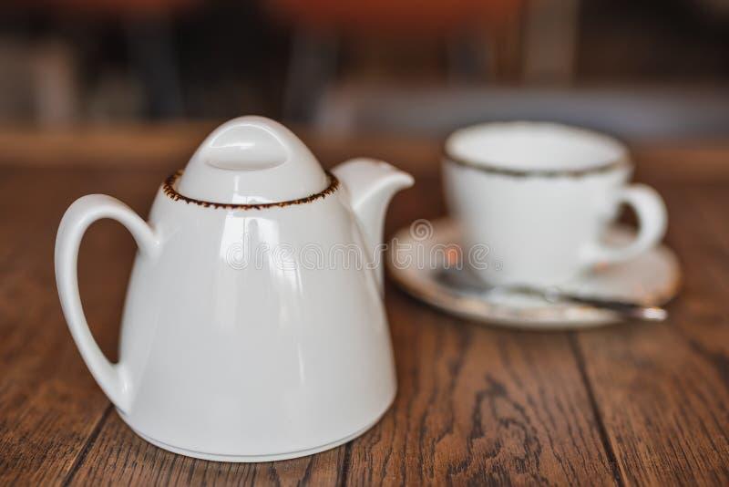 Teiera ceramica bianca e una tazza di invigorimento del tè fragrante fresco su una tavola di legno marrone fotografia stock libera da diritti
