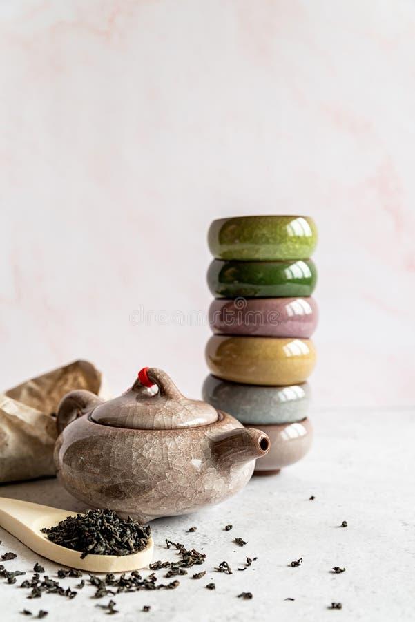 Teiera cinese con un mucchio dei tazza da the variopinti ed il pacchetto di tè su fondo di marmo bianco immagine stock