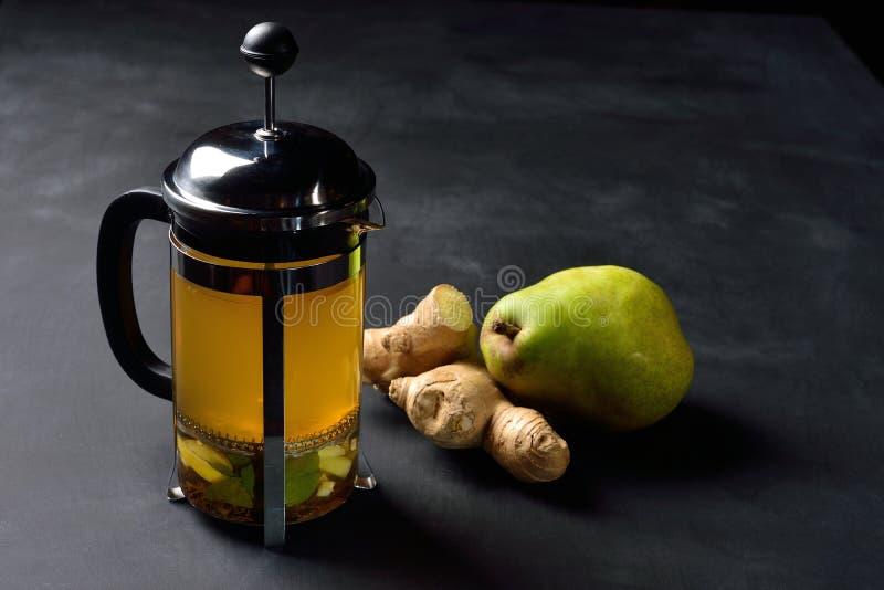 Teiera con il tè e la pera dello zenzero su fondo scuro fotografie stock