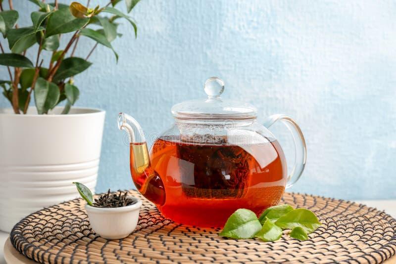 Teiera con le foglie asciutte e fresche aromatiche del tè, sulla stuoia di vimini fotografia stock