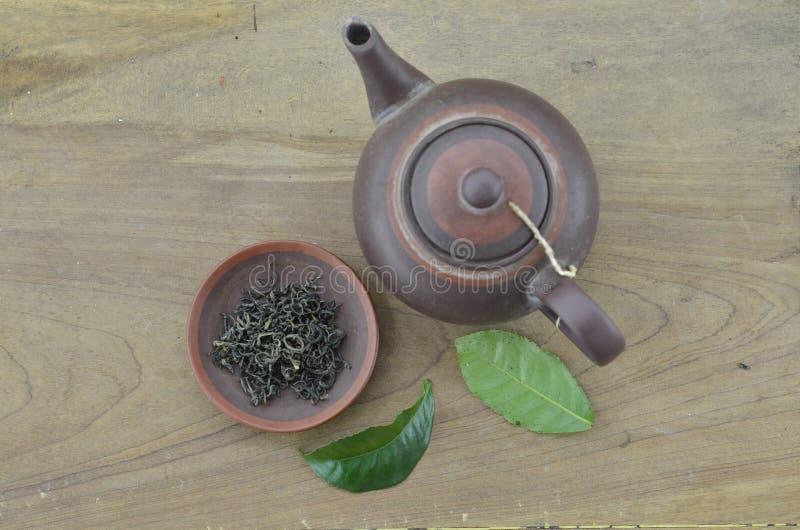 Teiera con tè asciutto e foglia verde fresca su fondo di legno fotografia stock libera da diritti