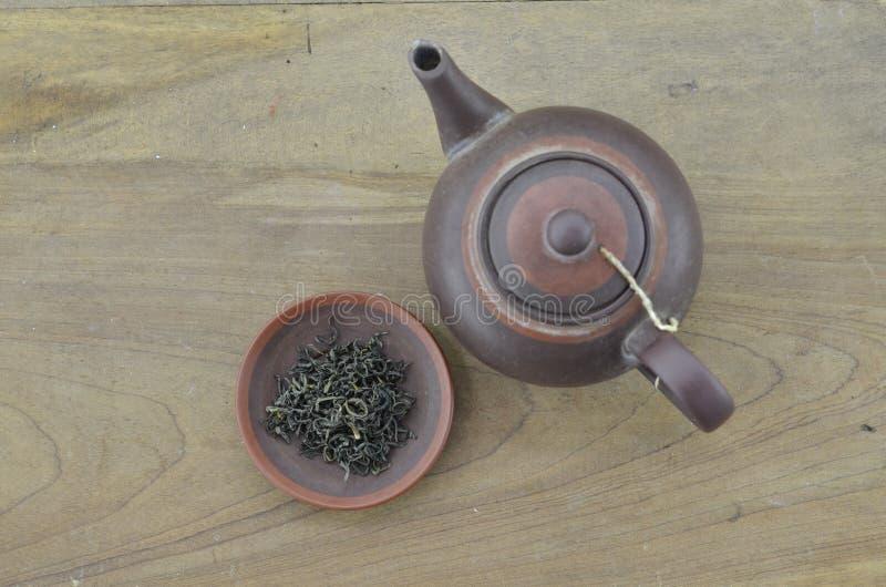 Teiera con tè asciutto in piatto su fondo di legno immagine stock libera da diritti