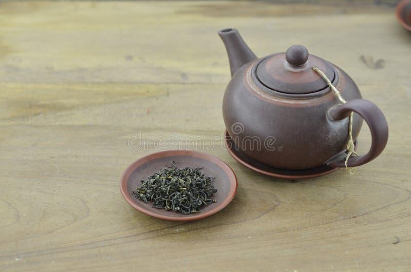 Teiera con tè asciutto in piatto su fondo di legno fotografia stock