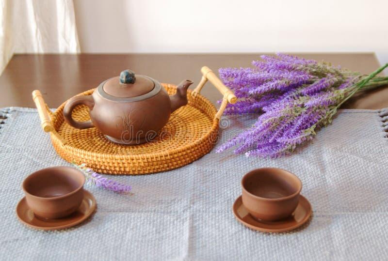 Teiera dell'argilla con le tazze sulla tavola, accanto a lavanda fotografie stock libere da diritti
