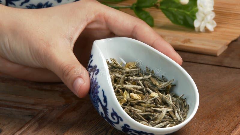 Teiera di vetro con il fiore di fioritura del tè dentro contro le foglie di tè verdi cinesi del fondo di legno vicino su in tradi fotografie stock libere da diritti