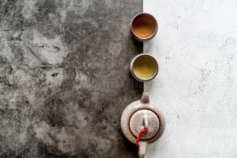 Teiera e tazza da the asiatici del tè sulla disposizione piana doppia bianca e nera di vista superiore del fondo fotografia stock libera da diritti