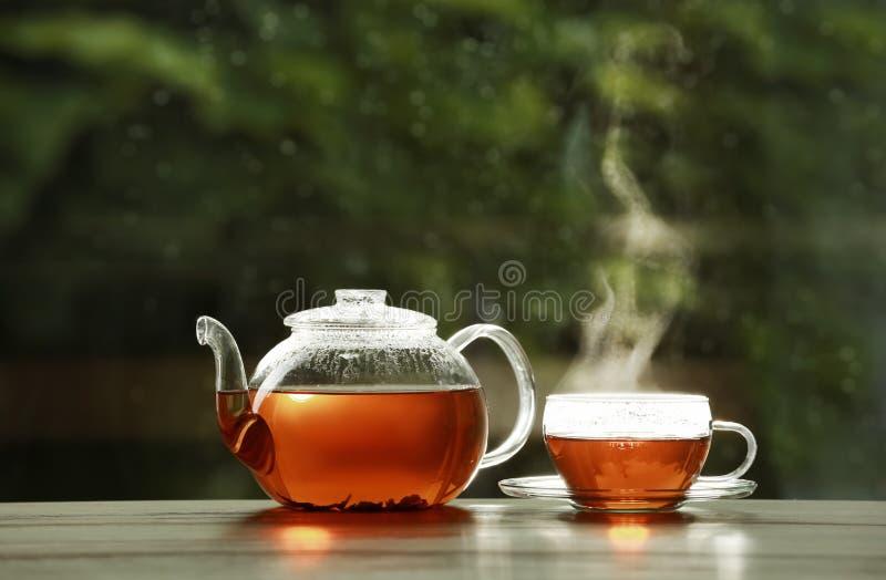Teiera e tazza di tè caldo sulla tavola di legno contro fondo vago immagine stock