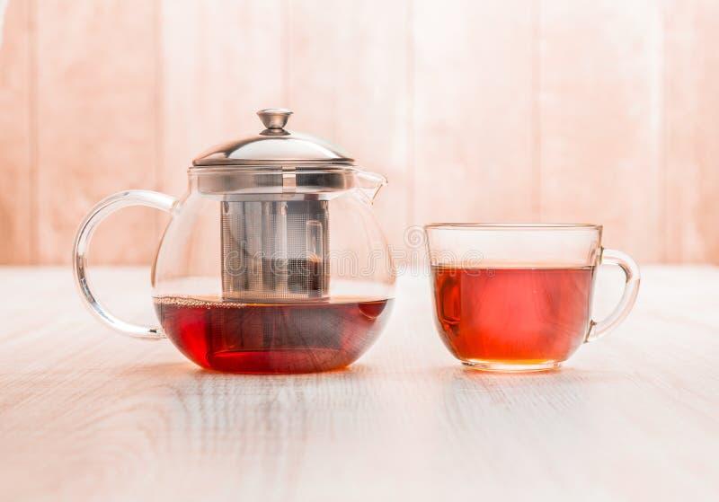 Teiera e tazza di tè sul fondo di legno della tavola fotografia stock libera da diritti
