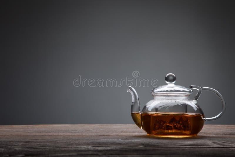 Teiera e tazza di tè sulla tavola di legno immagine stock