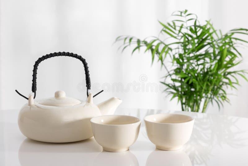 Teiera e tazze ceramiche sulla tavola fotografia stock