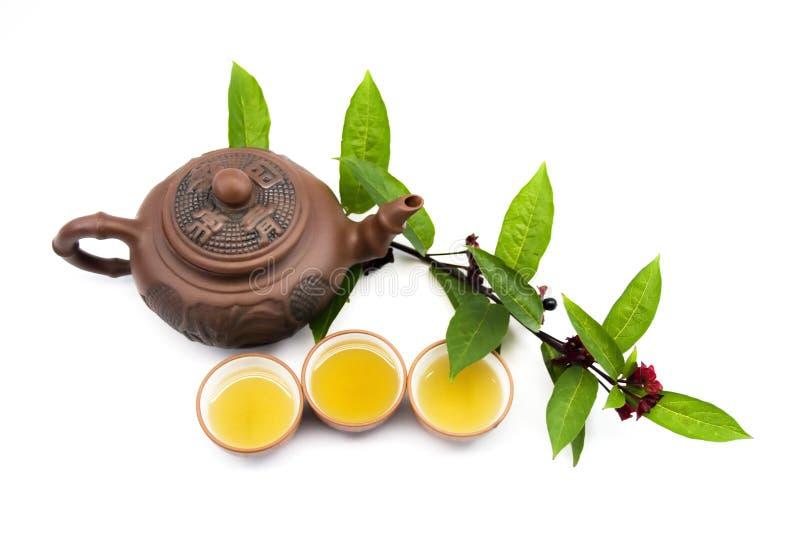 Teiera e tazze dell'argilla con le foglie di tè fotografia stock libera da diritti