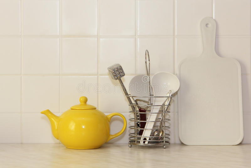 Teiera ed utensile ceramici gialli della cucina immagine stock