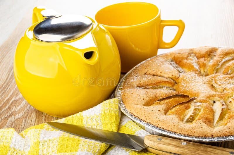 Teiera, tazza, torta dolce con le mele nella forma, coltello da cucina sul tovagliolo sulla tavola di legno fotografia stock